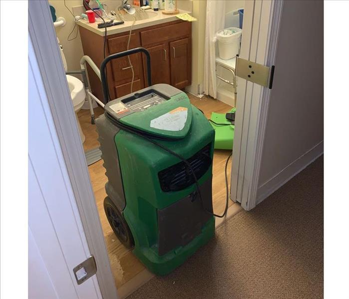 Dehumidifier and air mover drying the bathroom, no visible water