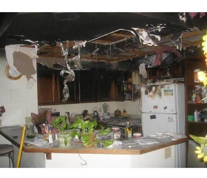 badly burned ceiling showing attic lumber, charred cabinets